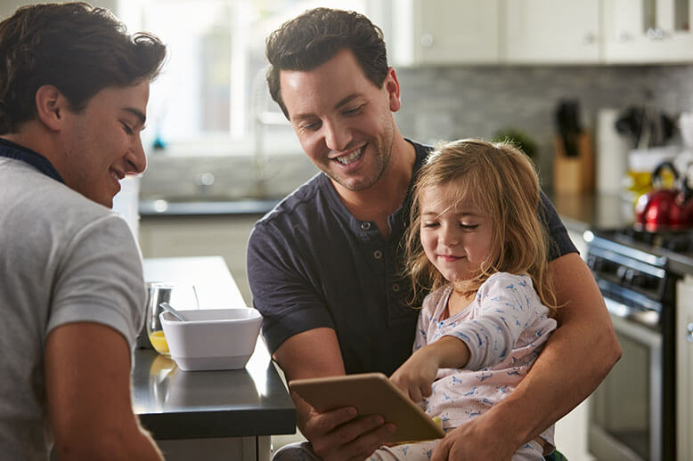 Two guys and one little child using a tablet